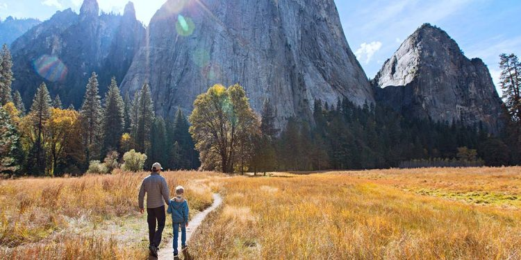 Man and child walking on single-track trail toward El Capitan in Yosemite