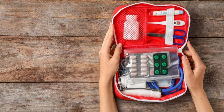 Someone holding an open first aid kit filled with pills, thermometer, stethoscope, scissors, etc.