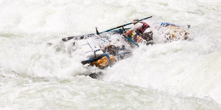 A wave-washed raft crashes through foamy whitewater rapids.