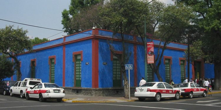 Blue house with cars parked along road