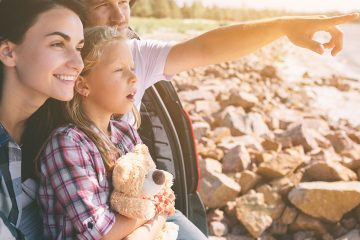 Parents and young daughter who is holding her teddy bear sitting in the back of a hatchback