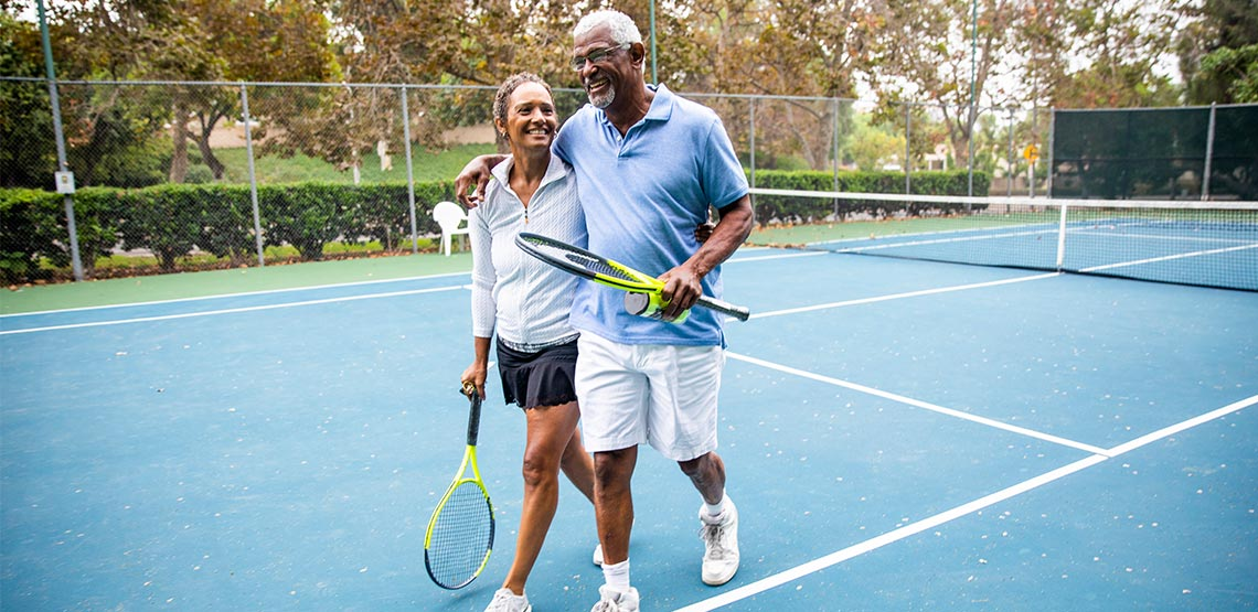 Two people walking off tennis court holding rackets