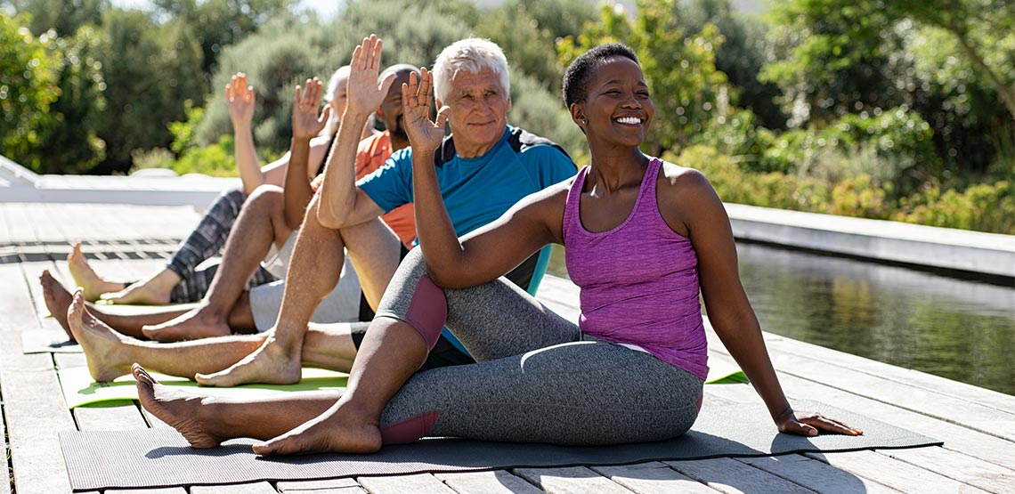 Four older people sitting on yoga mats outside
