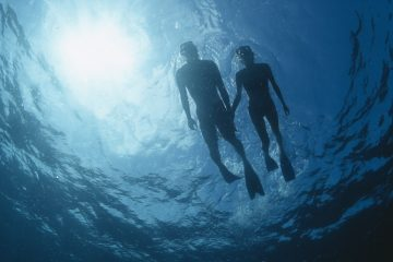 Seen from below, a couple snorkels on top of the waves, the sun a turquoise-blue above them.