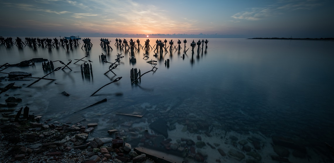The rising sun at Dry Tortugas National Park turns the water a pearlescent gray and casts the old pylons of a collapsed pier into stark relief.