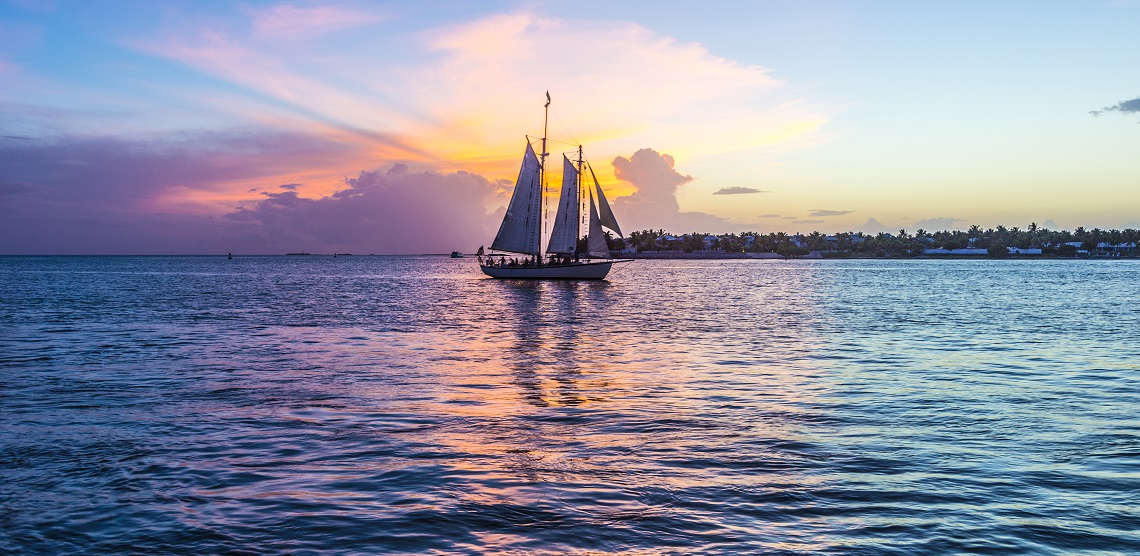 A three-sail sailboat slides by on calm waters at the sunset paints the sky in purples and pinks.