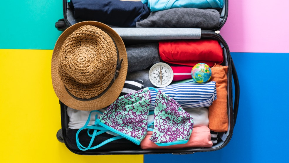 suitcase packed neatly with clothes, a hat and swimsuit on top