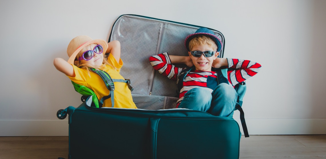 Two kids sitting in a suitcase wearing sunglasses