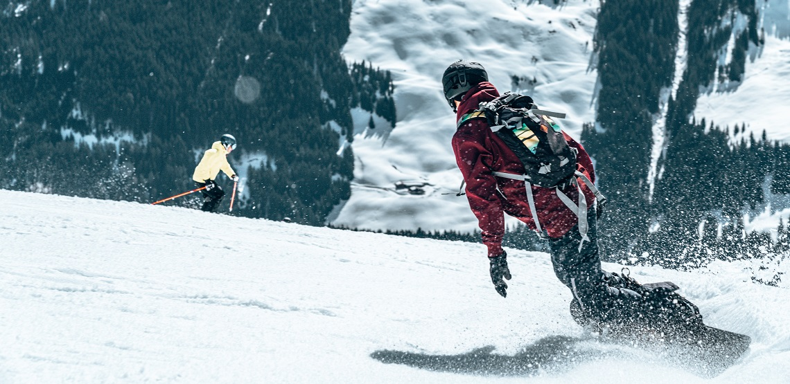 A snowboarder cuts across a snowy slope in the foreground while a skier dips over a ridge in the back.