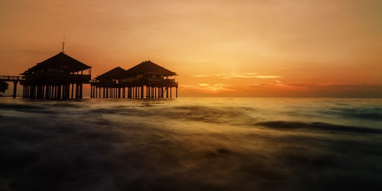 A group of stilt-borne villas rises above the sunset-gilded waves.