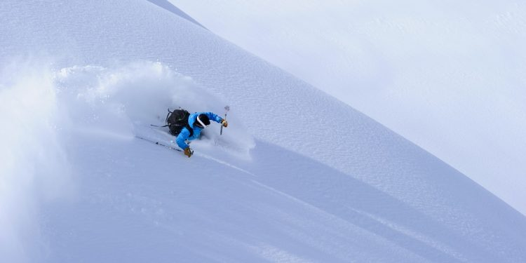 A skier shreds powder from an umarked slope.