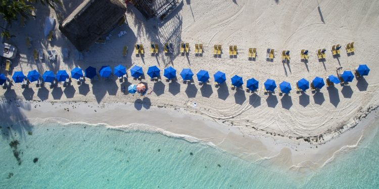 An aerial shot shows blue umbrellas dotting a white-sand beach.