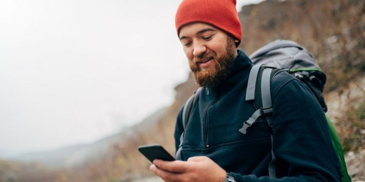 man looking at smart phone and wearing a backpack