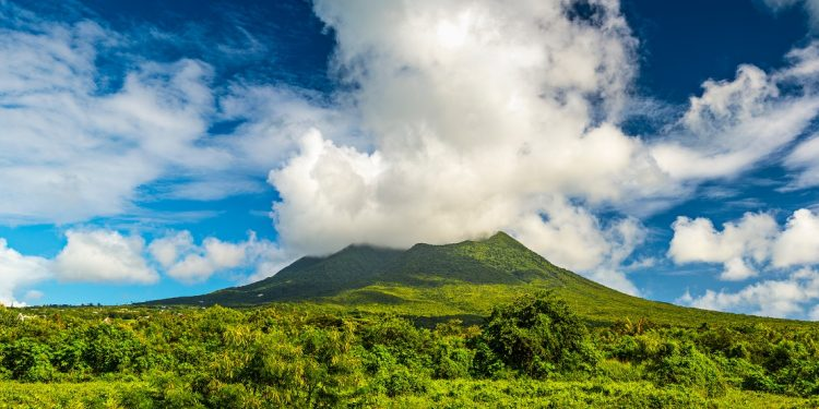 A cloudy cap rests on a green tropical mountain peak.