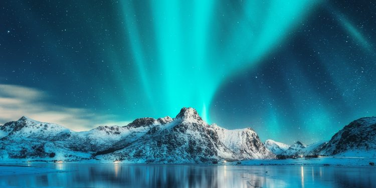 The eerie green glow of the aurora borealis gleams above a frozen lake and a snowy mountain.