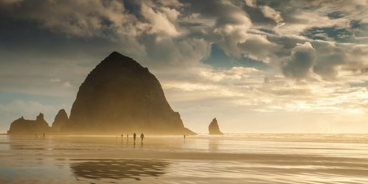 The titanic mass of Haystack Rock towers above the smooth sands of Cannon Beach, Oregon, and beachcombers stroll along the shore.