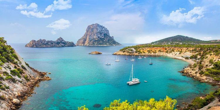 Ibiza landscape with teal waters and boats.