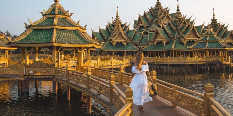 A lady in a white dress walking on a brown bridge.