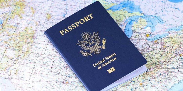 A blue passport laying on a map.