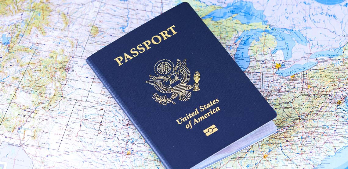 A blue passport laying on a map.