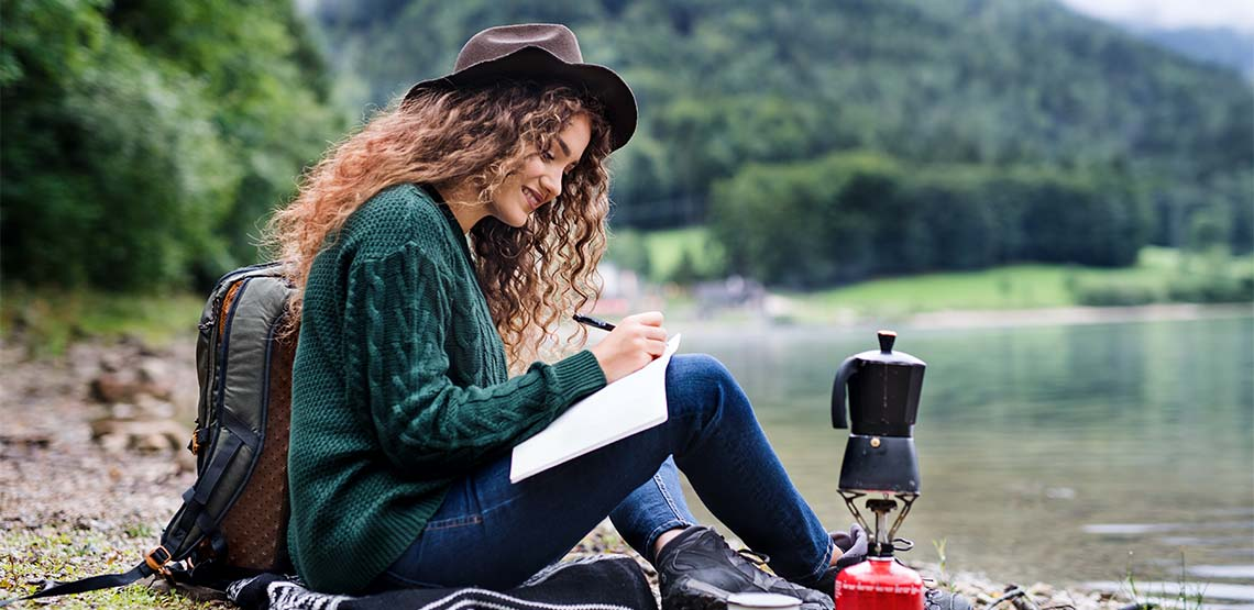 Someone sitting by the water near a forest writing in a travel journal.