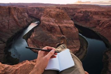A person with an open notebook in a rocky landscape.
