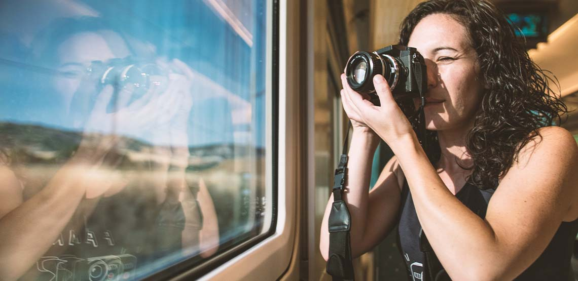 Someone using a camera to take a picture on a train.