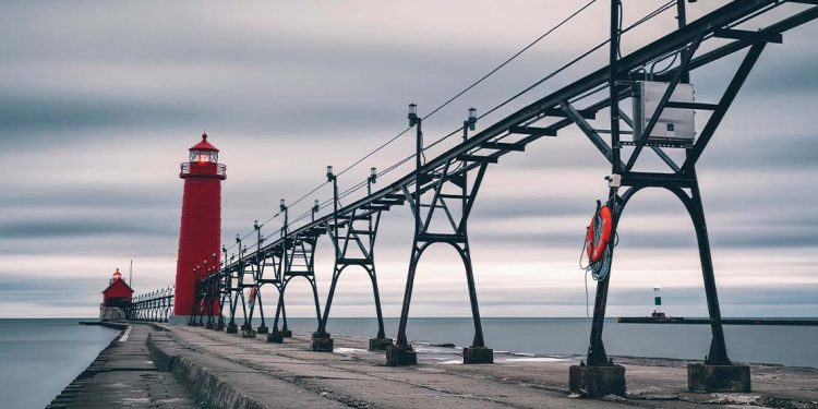 A red lighthouse at the end of a dock.