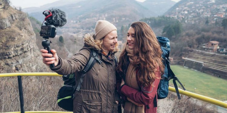 Two women standing on a mountain ledge holding up a camera to take a video.