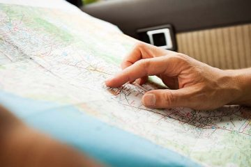 Someone pointing to a travel map.