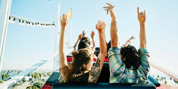 People riding on a rollercoaster with their arms up.