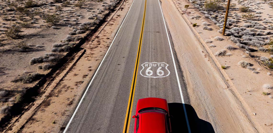 A red car driving on Route 66.