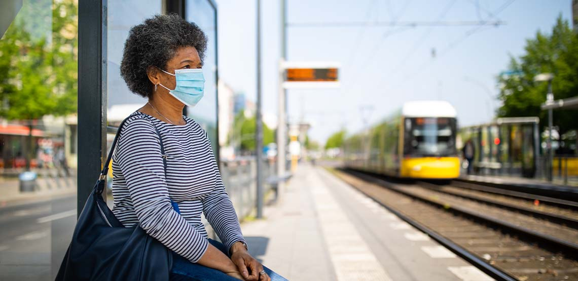 Someone wearing a mask while sitting waiting for a train.