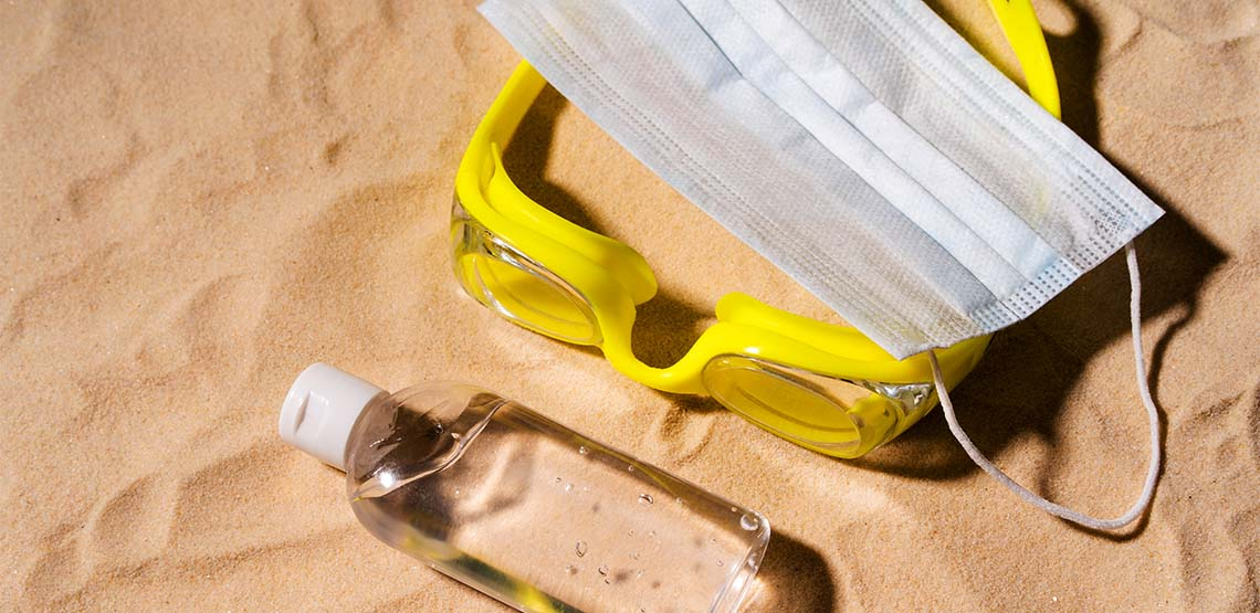 Yellow goggles, a bottle of hand sanitizer and a mask against sand on a beach.