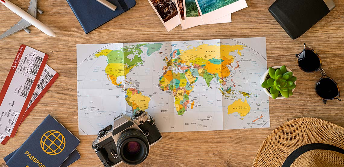 A travel flatlay with a travel map, camera, sunglasses and a passport.