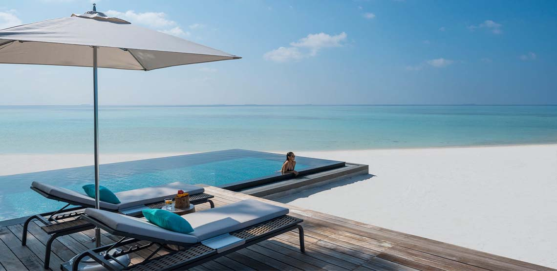 Someone swimming in an infinity pool on the beach of Voavah island.