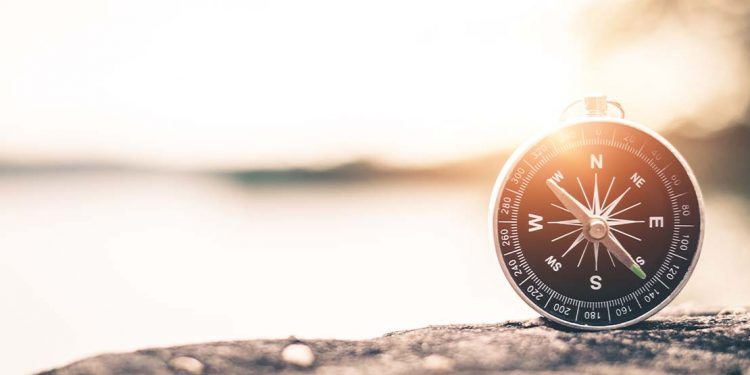 A compass sitting on a rock against a sunset.