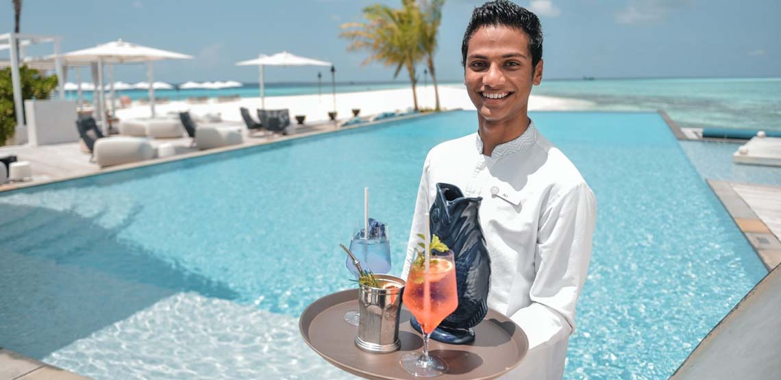 A man holding a tray of drinks in front of a pool.
