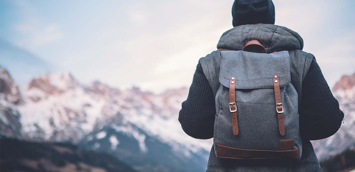 A man wearing a hiking backpack while looking at mountains.