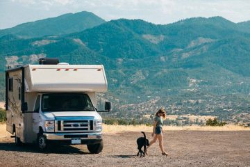 A women getting out of a white RV with her dog.