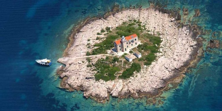 An overhead view of one of Croatia's private islands, with dark blue water and sandy beaches.