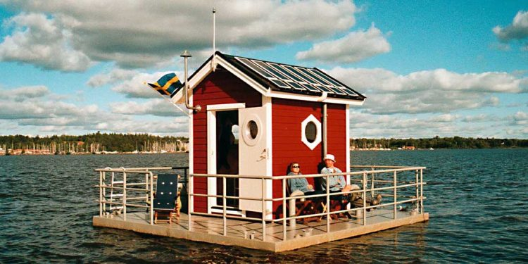 A little read house floating on the water with two people sitting on the deck.