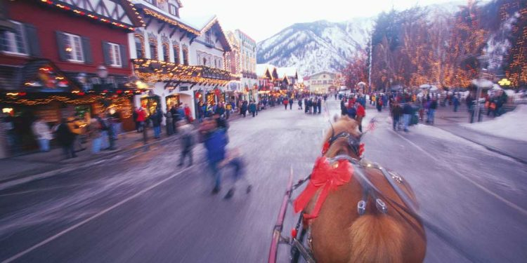 An in-motion snap shot of Leavenworth, Washington while someone is riding in a chariot.