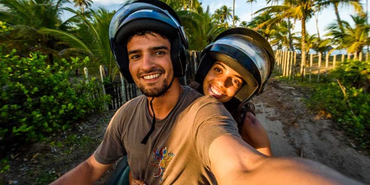 A couple on a stopped motorcycle taking a selfie.