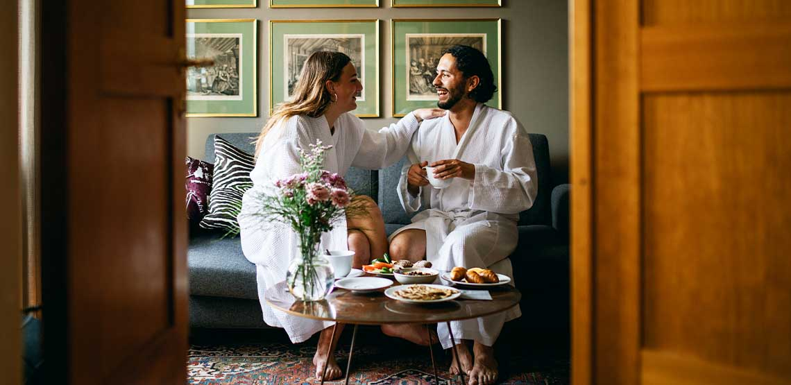 A couple sitting in a hotel room in bathrobes.