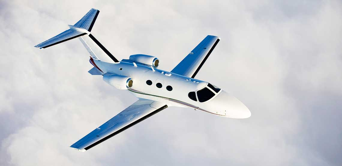A white private jet flying in the sky.