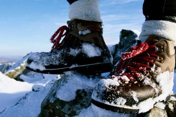 A person standing on a snowy mountain wearing brown hiking boots.