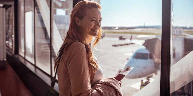 A woman standing near a window holding a plane ticket and smiling.
