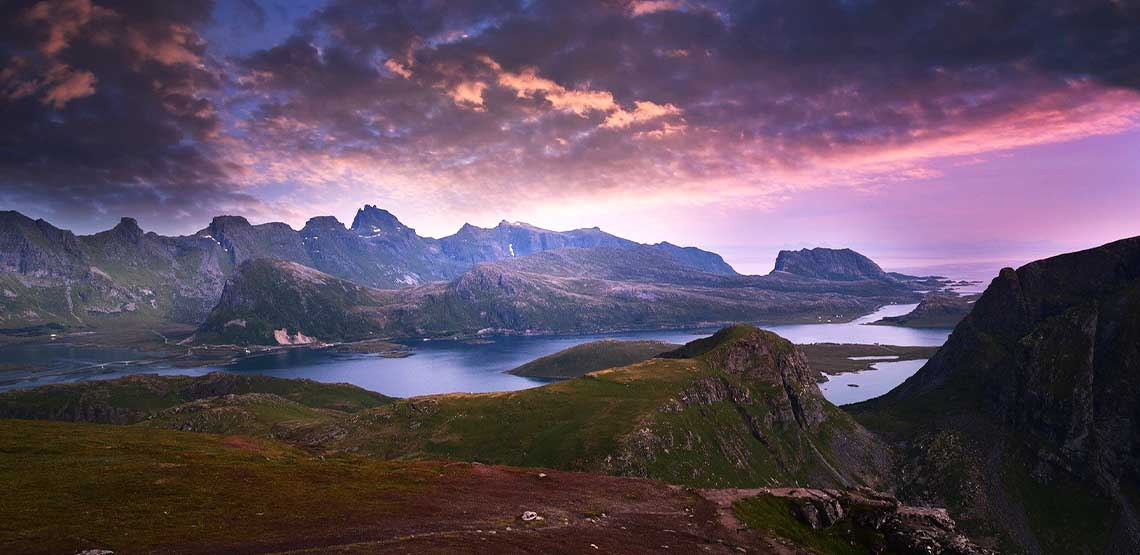 A lake surrounded by mountains basked in a purple hue.