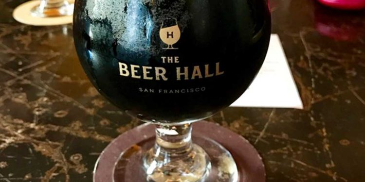 A cup of dark brown beer.